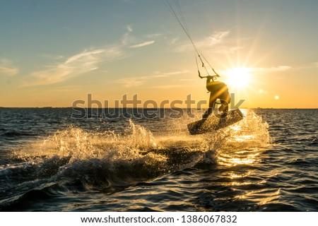 Photo of  kitesurfer doing tricks in sunset