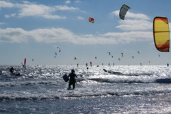 Kitesurfer starting in front of many windsurfers and kitesurfers at the ocean glistening in the sun, in backlight