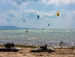 Kitesurfers preparing kiteboards at the beach. Other kiteboarders far from the coast compete in jumping and stunts and fly after the wind on their kites to the horizon. Sun shines through dense clouds