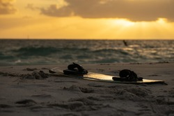 Kitesurfing board placing on the beach with defocused beautiful silhouette picture professional kite surfer surfing in the ocean sunsetting at the background
