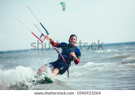 Photo of  Kitesurfing Kiteboarding action photos man among waves quickly goes