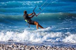 Kitesurfing. Kitesurfer rides the waves on high speed at the sunset