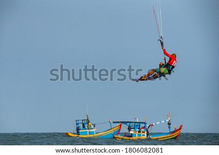 Photo of  Kitesurfing on the waves of the sea in Mui Ne beach, Phan Thiet, Binh Thuan, Vietnam. Kitesurfing, Kiteboarding action photos. Kitesurf In Action against vietnamese boats