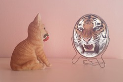 Kitten looks in the mirror and sees himself reflected like a tiger. Self-confidence concept. Business or personal growth.