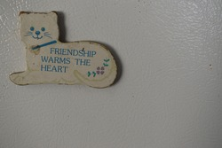 kitty cat fridge magnet friendship sign with cute phrase saying quote about friends stuck to white textured refrigerator door.