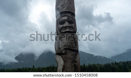 Kitwonga totem poles of British Columbia against dramatically cloudy sky