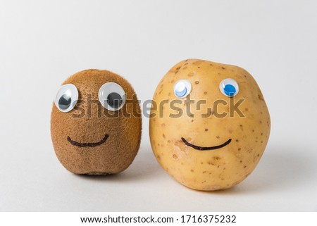 Kiwi and potatoes with funny faces and eyes on white background
