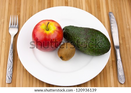 kiwi, avocado and apple on a white bowl with cutlery