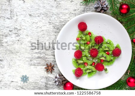 kiwi christmas tree with raspberries, pomegranate and coconut with pine cones. funny food idea for kids. Christmas and New Year food background. top view with copy space #1225586758
