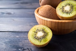 Kiwi fruit in a bowl on wooden background. Copy space