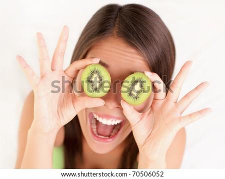 Kiwi. Healthy fruit funny woman holding kiwi fruit for her eyes.