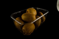 Kiwi in a box isolated on black background