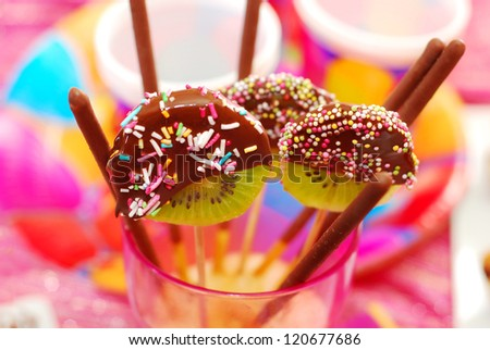 kiwi lollipops poured chocolate with colorful sprinkles on birthday party for children