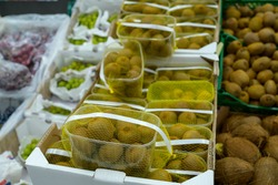 kiwi packaged in packages on a store counter, fruits in a supermarket