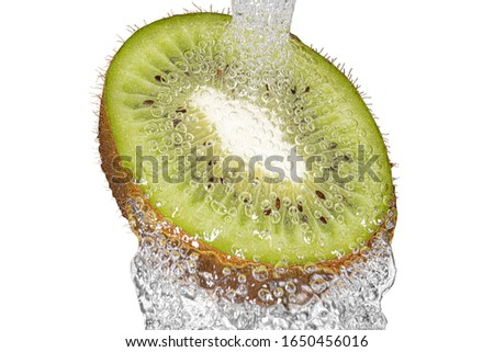 Kiwi placed under tap for washing.High resolution closeup of pulp and water drops