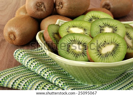 Kiwi slices in decorative bowl with whole kiwi fruit in the background. Close,up