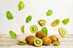 kiwi with flying slices on a wood background. tinting. selective focus