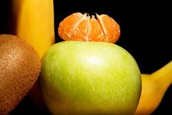 Kiwifruit, banana, tangerine slice and apple is close