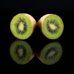 Kiwifruit on black reflective background