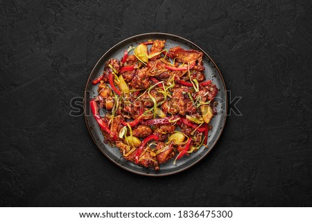 Kkanpunggi or Korean Spicy Garlic Fried Chicken on black plate on dark slate table top. Kan Pung Gi is korean and chinese cuisine dish. Typical asian food and meal. Top view Stockfoto ©