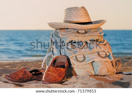 Knapsack, hat and sandal on the sandy beach
