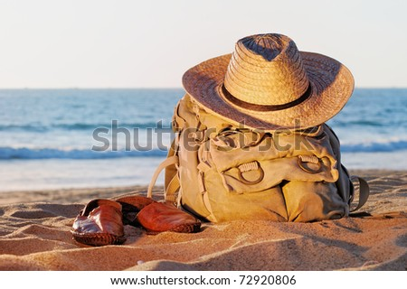 Knapsack, wicker hat and sandal on the sandy beach