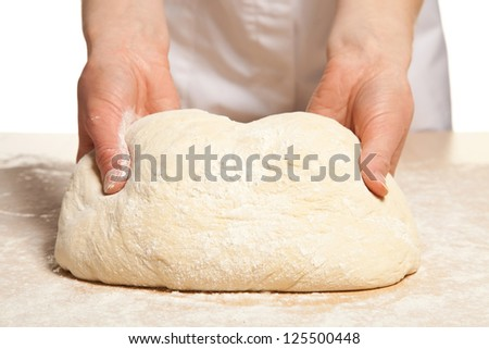Kneading dough; close-up of female hands in flour kneading dough