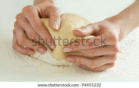 Kneading dough; close-up of female hands kneading dough