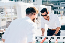 Knee figure of two modern bearded businessman playing table football during a break - having fun, break, playing concept