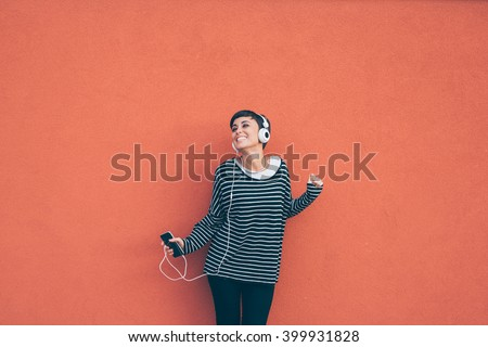 Knee figure of young beautiful caucasian woman listening music with headphones and smart phone hand hold, dancing, eyes closed smiling, leaning on a orange wall - music, happiness, technology concept #399931828