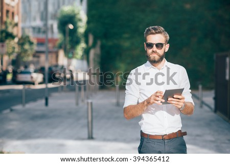 Knee figure of young handsome bearded businessman holding a tablet, looking over wearing sunglasses - technology, business, work concept, copy space left #394365412
