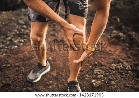 Knee injury on running outdoors. Man holding knee by hands close-up and suffering with pain. Sprain ligament or meniscus problem.