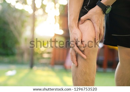 Knee pain .man stand at park  Her hand caught at the knee. Having painful feet and stretching muscles fatigue To relieve pain. health concepts.