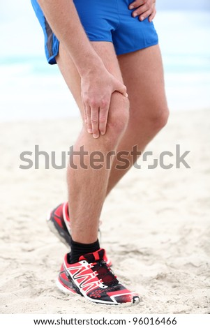 Knee pain - runner injury. Pain in knee joints in man running on beach.