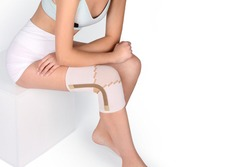 Knee Support Brace on leg isolated on white background. Orthopedic Anatomic Orthosis. Braces for knee fixation, injuries and pain. Orthotics. Foot orthosis. Knee Joint Bandage Sleeve. Elastic Sports