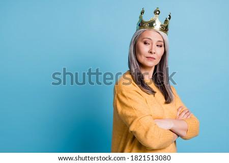 Kneel before queen. Photo of stunning gorgeous elegant senior lady arrogant look smug smile crown head watching servants clean house wear yellow jumper bright blue color background