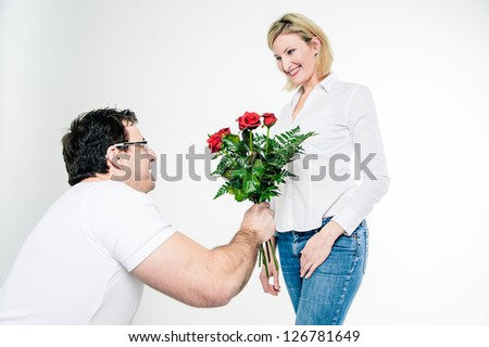 Kneeling man gives roses to his girlfriend