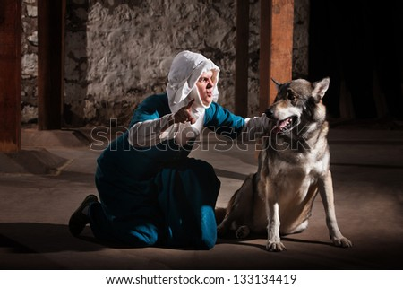 Kneeling middle ages nun character giving commands to a dog
