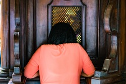 kneeling woman at the confessional confesses with the priest
