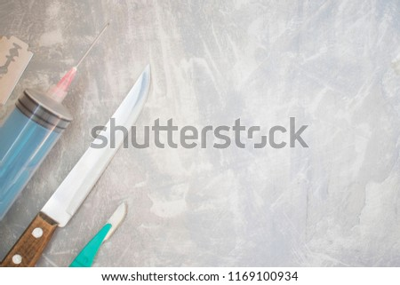 knife, a scalpel, a syringe on a concrete background. concept of sharp objects. save space. advertising space