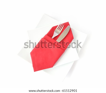 knife and fork in a red napkin on a white double square plate on a white background