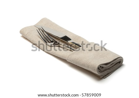 knife and fork in textile napkin - stock photo