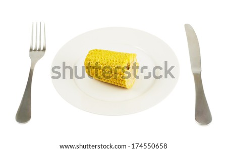 Knife and fork next to a plate with a cornstick piece isolated over white background