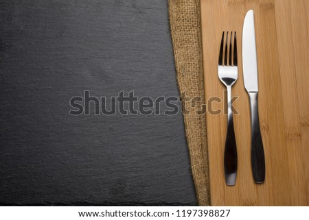 Knife and Fork on Slate and wood background #1197398827