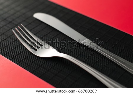 knife and fork on the on black table red napkins by the sides of the flatware