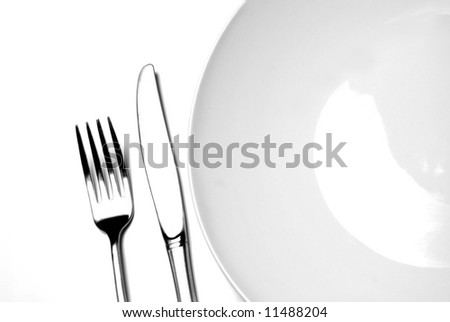 Knife and fork silverware with white plate on white background