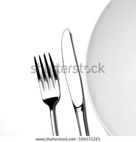 Knife and fork silverware with white plate setting on white