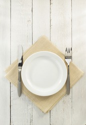 knife and fork with plate at napkin on wooden background