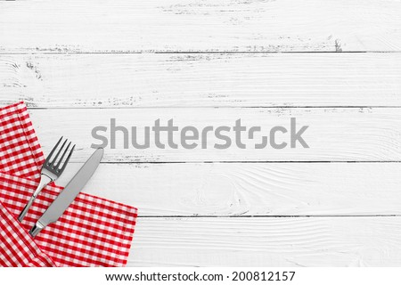knife and fork with red checked tablecloth and copyspace on white old vintage wooden table