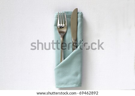 Knife and fork with serviette isolated on a white background